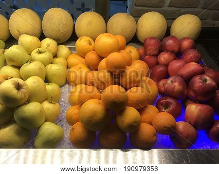 Mixed fruits background.  Oranges, yellow apples, melons and red apples