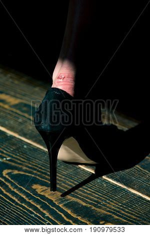 rub on leg in black fashionable shoe of glamour woman on wooden floor background beauty and fashion skincare