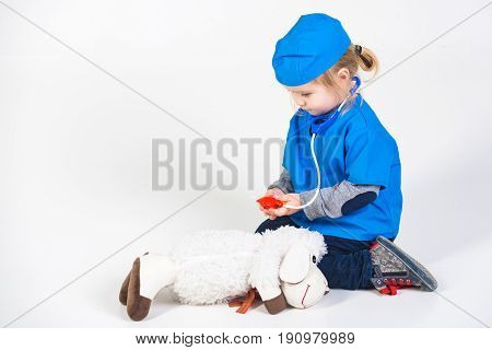 small boy in blue doctor uniform playing vet with toy animal of donkey in medical hospital isolated on white background medicine and healthcare copy space