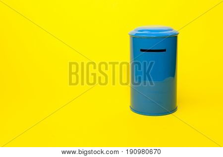 piggy bank or vintage retro blue post box shaped money box on yellow background financial business saving money concept selective focus