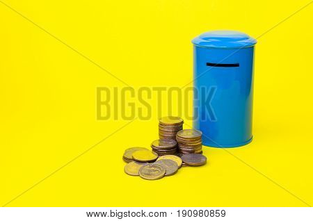 piggy bank or vintage retro blue post box shaped money box with money coin stack on yellow background financial business saving money concept selective focus