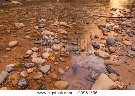 a stream flowing over rocks at sunrise in Zion National park Utah