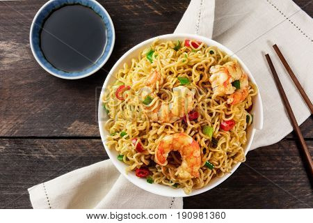 A bowl of instant Chinese noodles with green onions, red hot chilli peppers, and shrimps, shot from above on a dark rustic texture with a place for text, sauce, and chopsticks