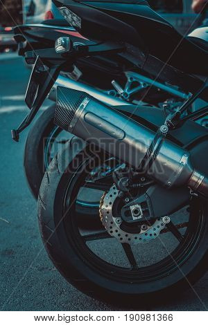 Close up shot of rear motorcycle wheel with tyre disk brake and exhaust pipe. all in black color. low light shot