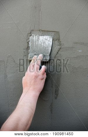 hand with metallic spatula plastering coat or layer of plaster stucco on cement wall surface texture on grey background. Working tool. Construction and renovation. Repairing and finishing work