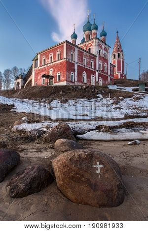 An old red church on the steep bank of the Volga River. Boulders in the foreground. On the boulders are painted crosses. Tutaev. Yaroslavl region. Russia.