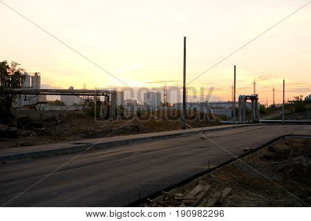 A new road under construction with pillars for future streetlights at dawn. The territory of the former ZIL plant. Moscow Russia.