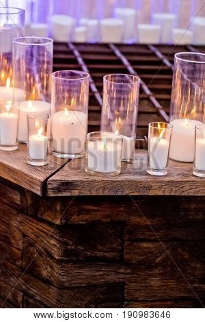 Candles in stylish glass candleholders burning with soft warm flame on wooden counter on blurred background. Warm interior. Lighting. Romantic decor and arrangements. Holidays celebration
