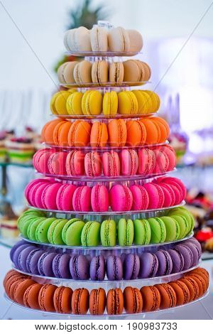 macaron cakes tasty french dessert on multilevel plastic stand or plate on blurred background. Food dieting. Birthday anniversary wedding celebration