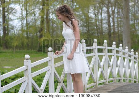 Young girl on a spring day standing on a bridge in her confirmation dress.