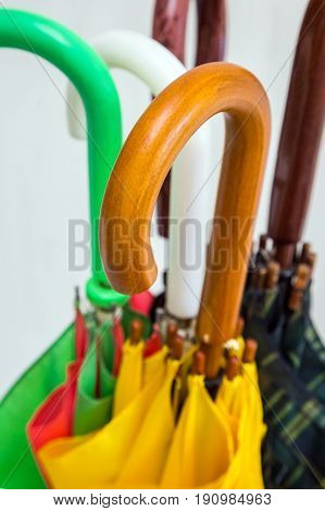 Umbrellas of different colors with handles view from above close-up on a white background