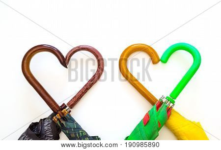 Creative image umbrellas of different colors with handles close-up heart symbol on white background holiday love