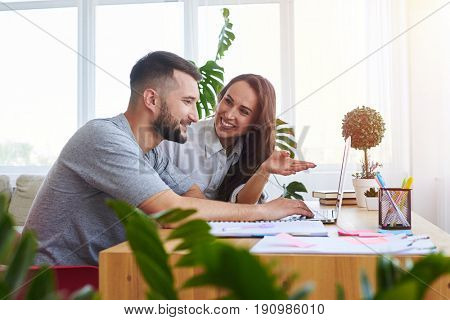 Wide shot of pleasant girlfriend showing something in laptop to boyfriend while sitting at table