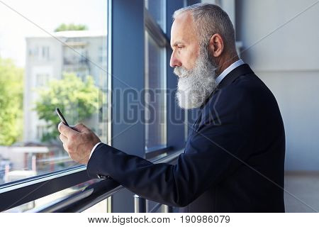 Mid shot of concentrated gentleman surfing in phone while leaning on handrail with copy space