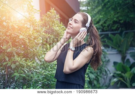 Beautiful young women in casual dress listen to music in parks and happy during the evening light.