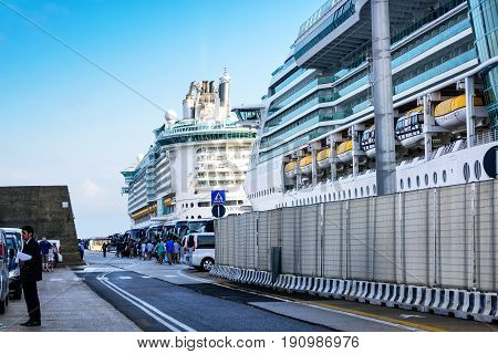 Rome Italy - June 10 2016: Cruise ships anchored in the port of Civitavecchia near Rome. Shuttles and buses lined on the street for passenger tours.