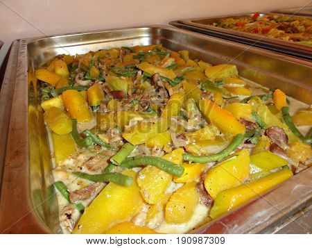 Mixed vegetables cooked in coconut milk metal tray holding mixed vegetables cooked in coconut milk, including squash, green beans, pork meat and more.
