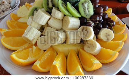 Slice fruits on a white plate An assortment of sliced fruits for dessert, including oranges, bananas, kiwi, grapes and pineapples