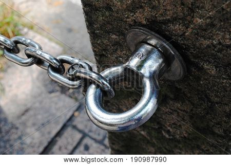 Shiny chain fastened to a hook, close up Close up of a strong silver chain fastened to a strong hook attached to a concrete pillar