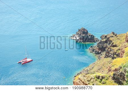View of the sea and a sailing catamaran from a steep coast of the island of Santorini Greece