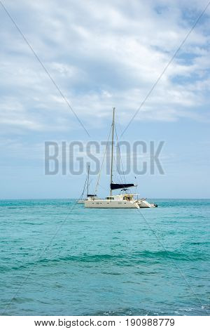White sailing catamarans in a turquoise sea against a cloudy sky background
