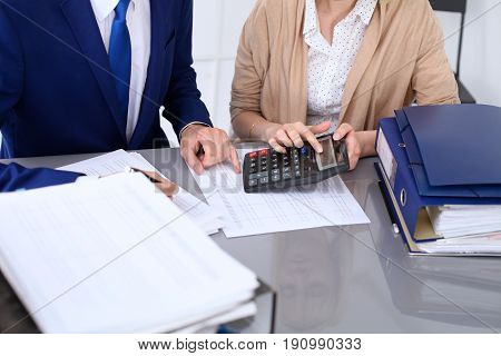 Bookkeeper or financial inspector and secretary making report, calculating or checking balance. Internal Revenue Service inspector checking financial document. Audit concept