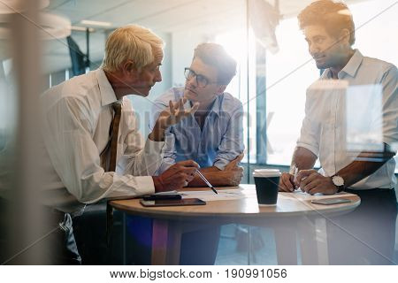 Three male executives standing and discussing around a table. Corporate professional having an informal meeting in modern office.