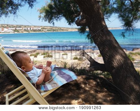 tree months old baby boy sitting on small sun bed in the shadow of the tree, on sandy beach, Malta, Mellieha bay