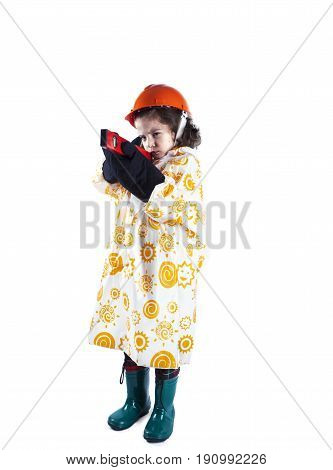 Cute Curly-haired Boy Builder In A Raincoat Holing A Building Level. Foreman In An Orange Constructi