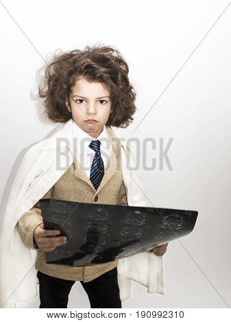 Little cute curly boy dressed in a business suit and a lab coat holding x-ray on gray background