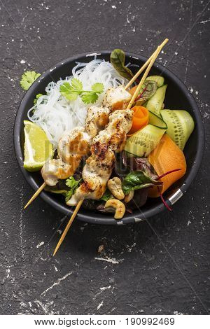 Cashew chicken skewer with noodles, fresh crisp vegetables and cilantro in a black bowl on a dark background. Top view