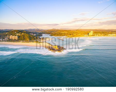 An aerial view of Currumbin Beach at sunrise with good lineup for the surfers