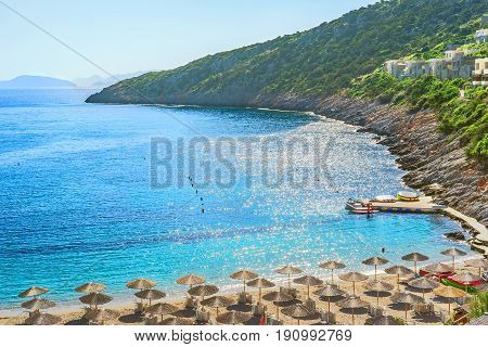 Picturesque landscape with the beach the sea and the steep banks of the island of Crete against the backdrop of a cloudless sky on a summer day