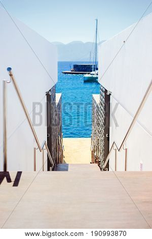 Stairway to the wharf between white stucco walls against the blue sea and sky