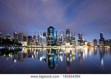 Brisbane City skyline at night with reflections on the Brisbane River.
