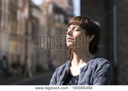 Beautiful young woman enjoying the sunlight outdoors in the city