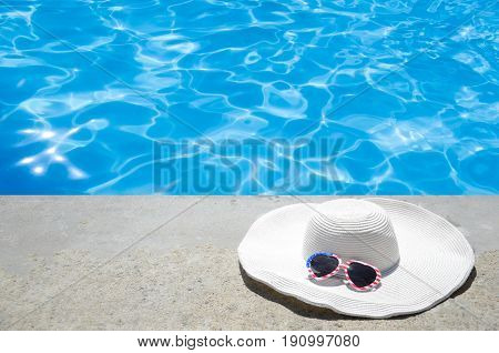 Summer background with white hat and sunglasses of American flag colors near the swimming pool
