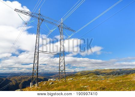 Power line structure installed over mountains with blue sky