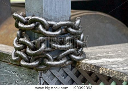 Gray metal chain coiled on a wooden post