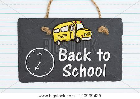 Back to School hand lettering text and school bus on weathered old chalkboard with retro lined paper