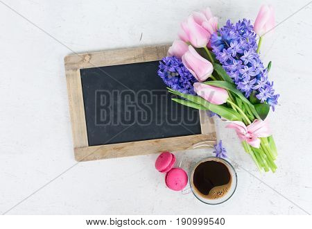 Pink tulips and blue hyacinths fresh flowers bouquet on white wooden table with empty blackboard