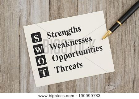 SWOT Strengths Weaknesses Opportunities Threats text on a card on weathered wood and a pen