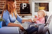 Little baby girl sits in high chair and makes the first attempt to eat with a spoon. Her beautiful mother is happy. Childhood and motherhood concept. Horizontal poster