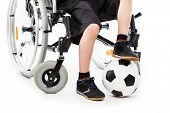 Invalid or disabled child boy sitting on wheelchair hand holding soccer sport ball white isolated poster