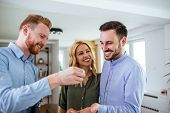 Lovely young couple buying a new house and receiving keys from consulting adviser. poster