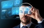 business, augmented reality and future technology concept - businessman working with transparent smartphone and virtual screens projections over black background poster