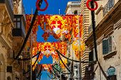 Festively decorated street with banners for St Augustine Feast in the old town of Valletta, Malta. Flaming, arrow pierced heart - symbol of St Augustine poster