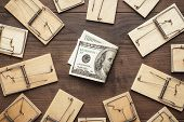 many mousetraps and money business concept. mousetraps surrounding money. starting business concept with money and traps near it. hard to earn money business concept. new business concept on brown wooden table. poster