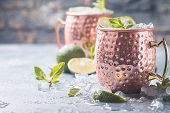 Moscow mule cocktail in copper cup with lime, ginger beer, vodka and mint garnish poster