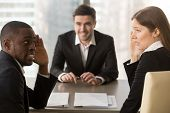 Multiracial confused employers covertly discuss job applicant, hide face with hands, look puzzled bewildered, secretly whisper during failed interview, bad negative first impression, make decision poster